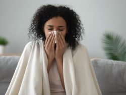 woman covered with blanket blowing nose got flu